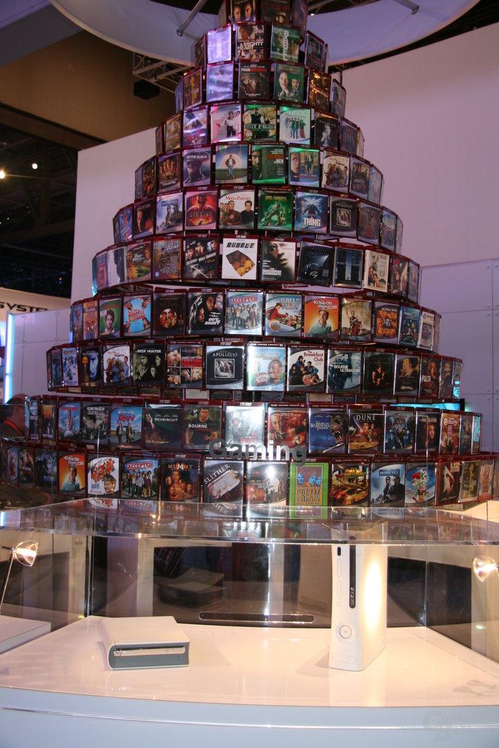 HD-DVD-Laufwerk für die Xbox 360 vor einer Wand aus HD-DVD-Filmen auf der CES