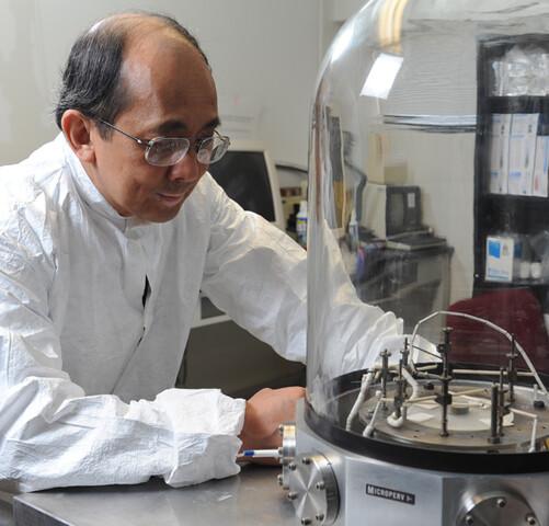 Weng Poo Kang mit einer Vakuumkammer zum Testen der Chips | Quelle: Joe Howell, Vanderbilt University