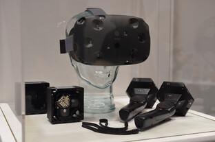 """HTC Vive mit zwei """"Lighthouse""""-Basisstationen (links) und kabellosen VR-Controllern (rechts)"""