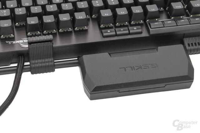 Der Behälter kann am Rahmen der Tastatur befestigt werden