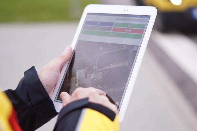 DHL-Mitarbeiter koordiniert Fahrzeug über Tablet