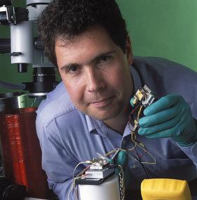 NIST-Physiker John Kitching zeigt das Herz der weltweit kleinsten Atomuhr